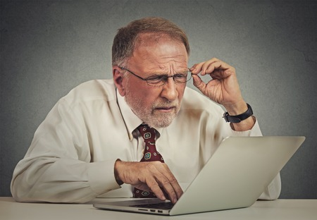 Photo pour Closeup portrait senior elderly mature business man with glasses having eyesight problems confused with laptop software isolated gray background. Age related changes. technology and senior people - image libre de droit