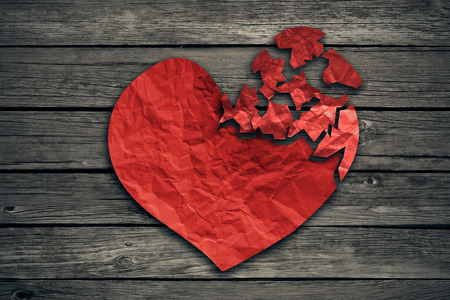Foto de Broken heart breakup concept separation and divorce icon. Red crumpled paper shaped as a torn love on old wood symbol of medical cardiovascular health care problems due to illness - Imagen libre de derechos