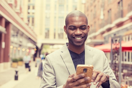Photo for Young happy smiling urban professional man using smart phone. Businessman holding mobile smartphone using app texting sms message wearing jacket - Royalty Free Image