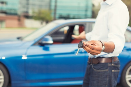 Foto per Male hand holding car keys offering new blue car on background - Immagine Royalty Free