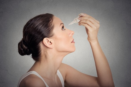 Foto de Side profile young woman applying eye drops isolated on gray wall background - Imagen libre de derechos