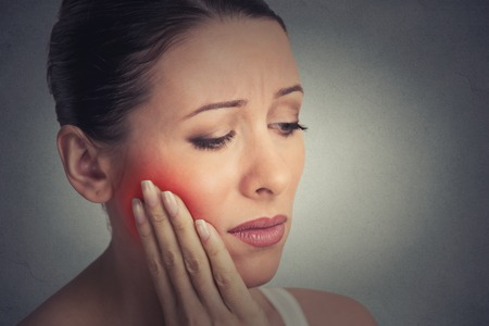 Foto de Closeup portrait young woman with sensitive tooth ache crown problem about to cry from pain touching outside mouth with hand isolated grey wall background. Negative emotion facial expression feeling - Imagen libre de derechos