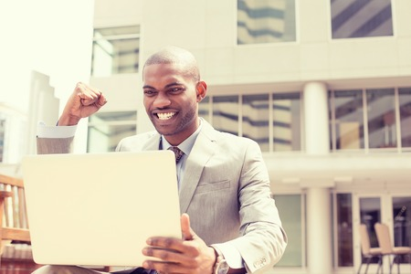 Photo for Happy successful young man with laptop computer celebrates success outside corporate office - Royalty Free Image