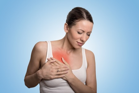 Photo pour Young woman with chest breast pain colored in red isolated on blue background - image libre de droit