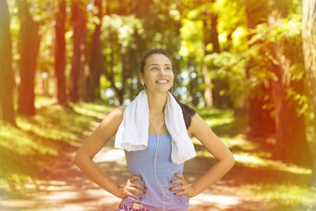 Foto de Portrait young attractive smiling fit woman with white towel resting after workout sport exercises outdoors on a background of park trees. Healthy lifestyle well being wellness concept - Imagen libre de derechos