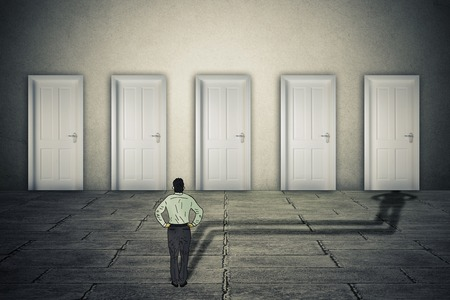 Foto de Making a choice opportunity concept. Businessman facing group of career opportunities with his cast shadow preferring or choosing one door entrance symbol for odds of success. - Imagen libre de derechos