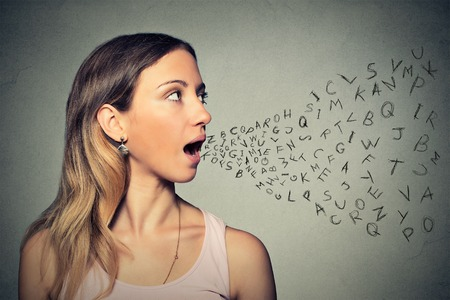 Foto de Woman talking with alphabet letters coming out of her mouth.  - Imagen libre de derechos
