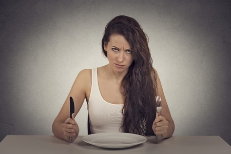Photo pour Young skeptical dieting woman tired of diet restrictions looking at camera sitting at table with empty plate with fork and knife. - image libre de droit