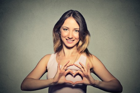 Foto de Closeup portrait smiling cheerful happy young woman making heart sign with hands isolated grey wall background.  - Imagen libre de derechos