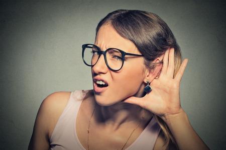 Foto de Closeup portrait young nosy woman hand to ear gesture trying carefully intently secretly listen in on juicy gossip conversation news  isolated gray background.  - Imagen libre de derechos