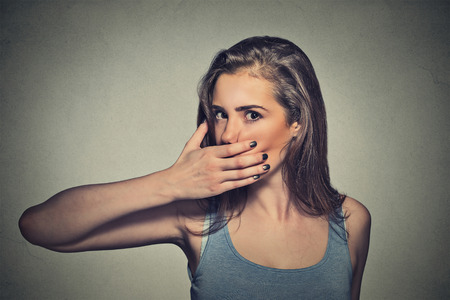 Photo pour Closeup portrait of scared young woman covering with hand her mouth isolated on gray wall background - image libre de droit