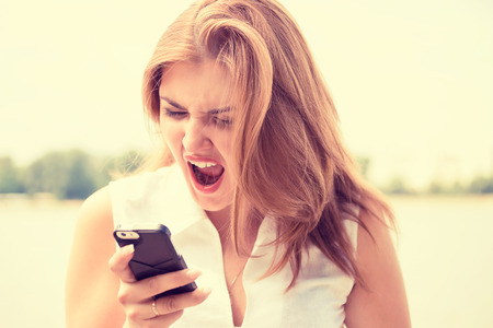 Portrait angry young woman screaming on mobile phone standing outside with city background. Negative emotions feelings