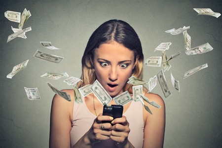 Foto de Technology online banking money transfer, e-commerce concept. Shocked young woman using smartphone with dollar bills flying away from screen isolated on gray wall office background. - Imagen libre de derechos