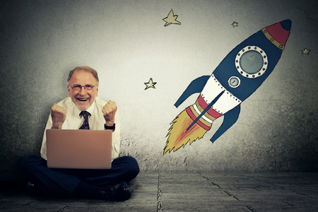 Foto de Excited senior man with high risky goals targets working on laptop computer on a starry wall background. Successful adventure concept - Imagen libre de derechos