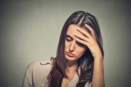 Foto de portrait stressed sad young woman looking down isolated on gray wall background - Imagen libre de derechos