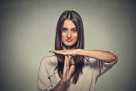 Foto de Closeup portrait, young, happy, smiling woman showing time out gesture with hands isolated on gray wall background. Positive human emotion facial expressions, feeling body language reaction, attitude - Imagen libre de derechos
