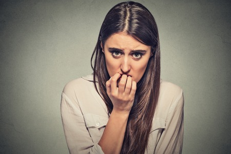 Foto de Closeup portrait young unsure hesitant nervous woman biting her fingernails craving for something or anxious, isolated on gray wall background. Negative human emotions facial expression feeling - Imagen libre de derechos