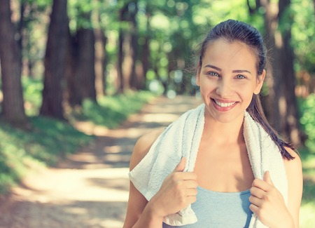 Photo pour Portrait young attractive smiling fit woman with white towel resting after workout sport exercises outdoors on a background of park trees. Healthy lifestyle well being wellness happiness concept - image libre de droit