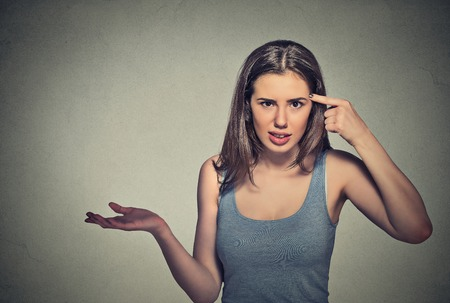 Photo pour Closeup portrait of angry mad young woman gesturing with her finger against temple asking are you crazy? Isolated on gray wall background. Negative emotions facial expression feeling body language - image libre de droit