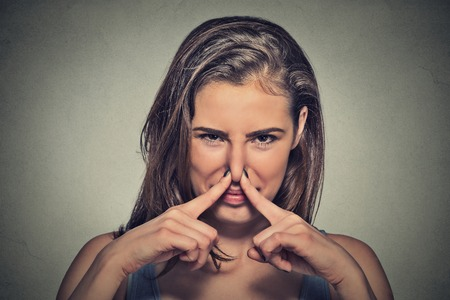 Photo pour Closeup portrait headshot woman pinches nose with fingers hands looks with disgust something stinks bad smell situation isolated on gray wall background. Human face expression body language reaction - image libre de droit