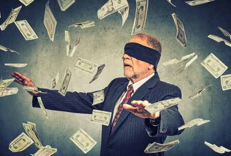 Photo pour Blindfolded senior businessman trying to catch dollar bills banknotes flying in the air on gray wall background. Financial corporate success or crisis challenge concept - image libre de droit