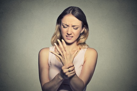 Young woman holding her painful wrist isolated on gray wall background. Sprain pain