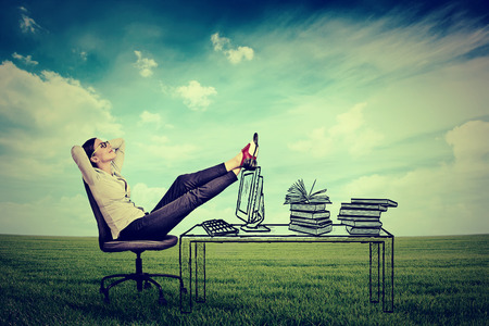 Photo for young businesswoman relaxing sitting in the office in the middle of a green meadow. Stress free working environment concept - Royalty Free Image