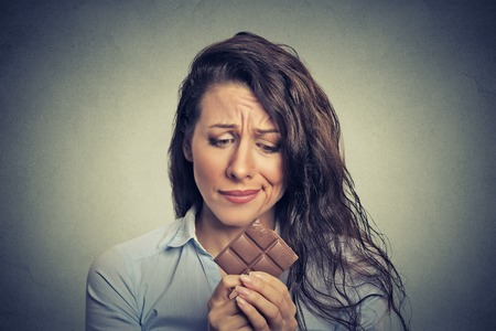 Foto per Portrait sad young woman tired of diet restrictions craving sweets chocolate isolated on gray wall background. Human face expression emotion. Nutrition concept. Feelings of guilt - Immagine Royalty Free