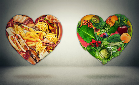 Photo pour Diet choice dilemma and heart health concept. Two hearts one shaped of green vegetables fruit and alternative one made of  fatty junk high calorie food. Heart disease and food medical health care - image libre de droit