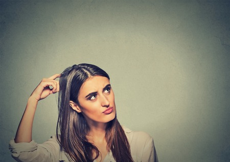 Foto de Contused thinking woman bewildered scratching her head seeks a solution isolated on gray wall background. Young woman looking up - Imagen libre de derechos