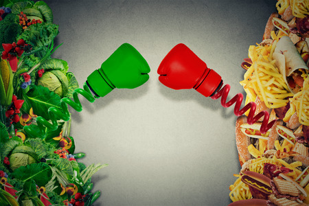 Foto per Vegetarian food fighting unhealthy junk food with boxing gloves punching each other. Diet battle nutrition concept. - Immagine Royalty Free