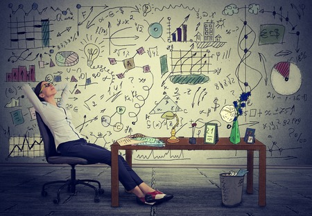 Photo for Young business woman relaxing at her desk in her office - Royalty Free Image