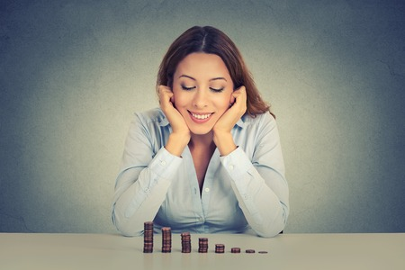 Photo pour Young successful business woman sitting at table looking at growing stack of coins. Financial freedom target success concept - image libre de droit