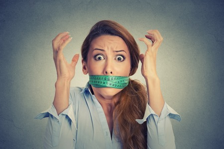 Diet restriction and stress concept. Portrait of young frustrated woman with a green measuring tape around her mouth isolated on gray wall background. Face expression emotion