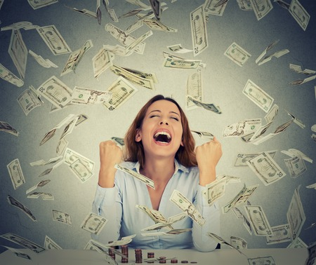 Foto de Excited happy young woman sitting at table with growing stack of coins under a money rain isolated on gray wall background. Positive emotions financial success luck good economy concept - Imagen libre de derechos