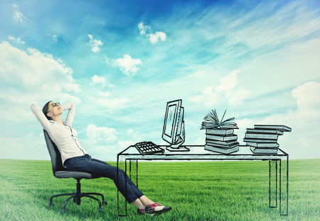 Photo for young successful businesswoman relaxing sitting in the office at her desk in the middle of a green meadow. Stress free working environment concept - Royalty Free Image