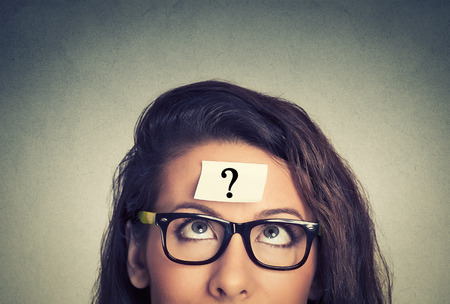 Foto de thinking woman with question mark on gray wall background - Imagen libre de derechos
