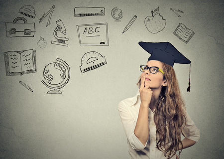 Foto de Young beautiful business woman with graduation hat looking up thinking about education isolated on gray wall background - Imagen libre de derechos