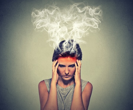 Foto de Portrait young stressed woman thinking too hard steam coming out up of head isolated on grey wall background. Face expression emotion perception. Burnout concept - Imagen libre de derechos