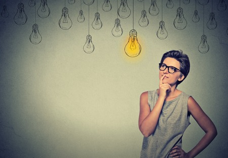 Foto de Big idea. Happy smart girl with glasses and solution lightbulb above head. Solving a problem creative idea concept - Imagen libre de derechos
