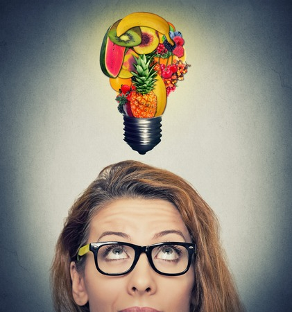 Foto per Eating healthy idea and diet tips concept. Closeup portrait headshot woman looking up light bulb made of fruits above head on gray wall background. - Immagine Royalty Free