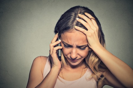 Foto de Portrait unhappy young woman talking on mobile phone looking down. Human face expression, emotion, bad news reaction - Imagen libre de derechos