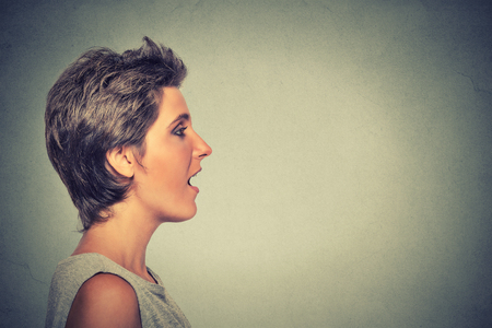Foto de Closeup side view profile portrait woman talking with sound coming out of her open mouth isolated grey wall background. Human face expression emotions. Communication, information, intelligence concept - Imagen libre de derechos