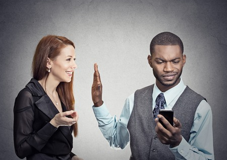 Foto de Attractive woman being ignored stopped by young handsome man looking at smartphone reading browsing internet isolated on gray wall background. Phone addiction concept. Human face expression emotions - Imagen libre de derechos