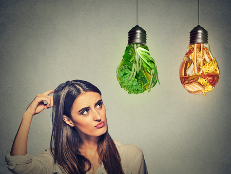 Foto de Portrait beautiful woman thinking looking up at junk food and green vegetables shaped as light bulb isolated on gray background. Diet choice right nutrition healthy lifestyle concept - Imagen libre de derechos