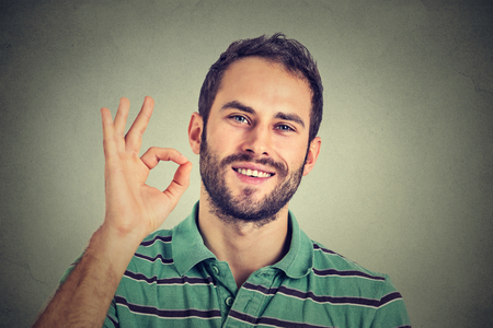 Photo pour man gesturing OK sign isolated on gray wall background - image libre de droit