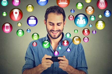 Photo for communication technology mobile phone high tech concept. Happy man using texting on smartphone social media application icons flying out of cellphone isolated grey wall background. 4g data plan - Royalty Free Image