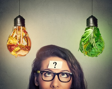 Foto de Woman in glasses question mark on head thinking looking up at junk food and green vegetables shaped as light bulb isolated on gray background. Diet choice right nutrition healthy lifestyle concept - Imagen libre de derechos