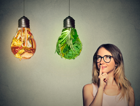 Foto per Portrait beautiful woman in glasses thinking looking up at junk food and green vegetables shaped as light bulb isolated on gray background. Diet choice right nutrition healthy lifestyle concept - Immagine Royalty Free