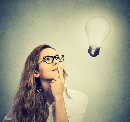 Foto per Closeup beautiful girl thinks looking up at bright light bulb isolated on gray wall background. Idea, business, education and people concept. Face expression - Immagine Royalty Free